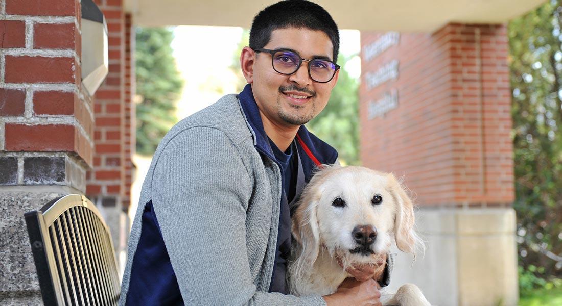 Neil Sinha outside WSU's Veterinary Medicine Hospital with his dog Molly.